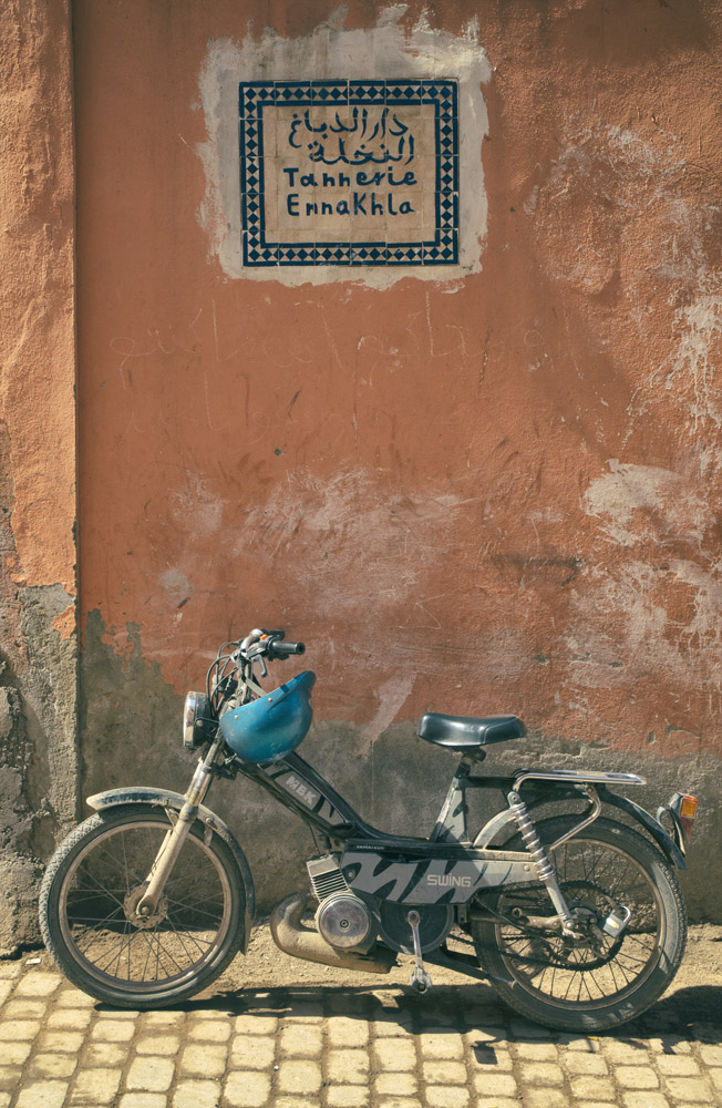 A motorbike standing next to a pink wall in the Marrakech Medina, Morocco.