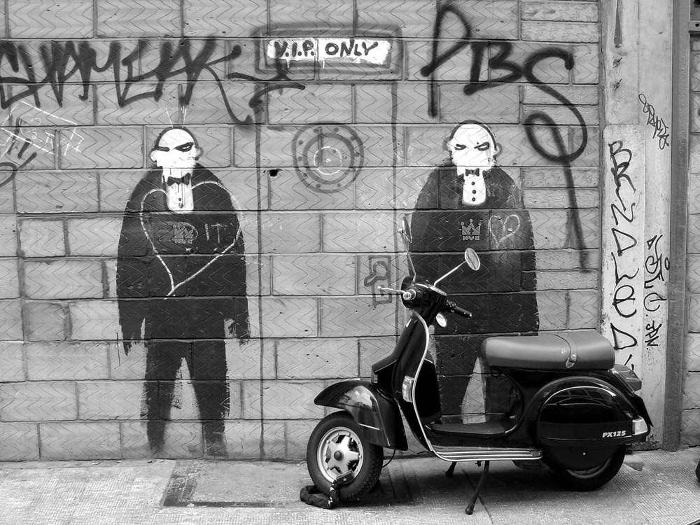 A Vespa PX125 parked up against a wall covered in graffiti, Shoreditch, London, United Kingdom