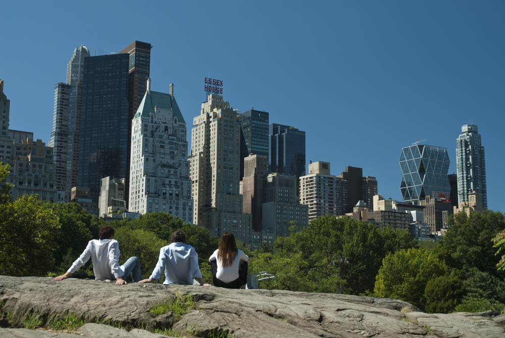 3 people relaxing in the urban oasis that Central Park is, New York City, US.